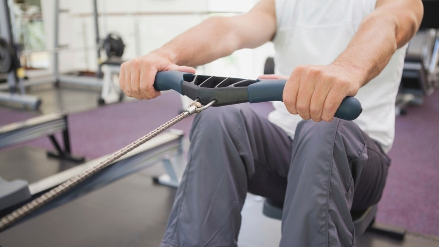 A man uses a rowing machine at the gym.