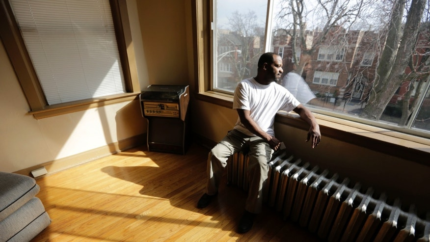 "In this March 8, 2016 photo, Darnell Johnson, 50, a resident of a sober home in Chicago, looks out the window of his apartment. Johnson says he was a ""weekend social drinker, but it would last all day."" Now when he smells alcohol or sees how it affects others, he remembers the bad times. (AP Photo/M. Spencer Green)"