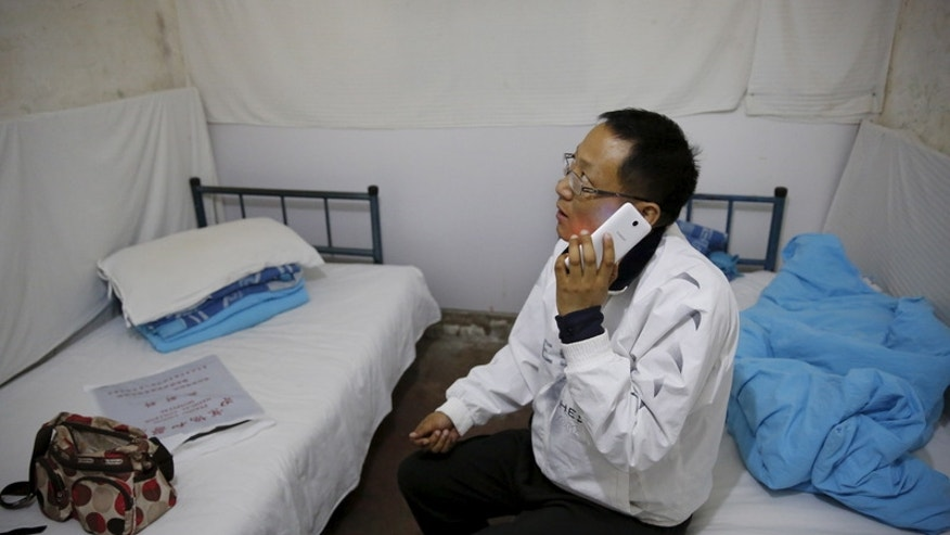 Cancer patient Cao Dongxian uses a mobile phone at a hotel room during an interview with Reuters in Beijing