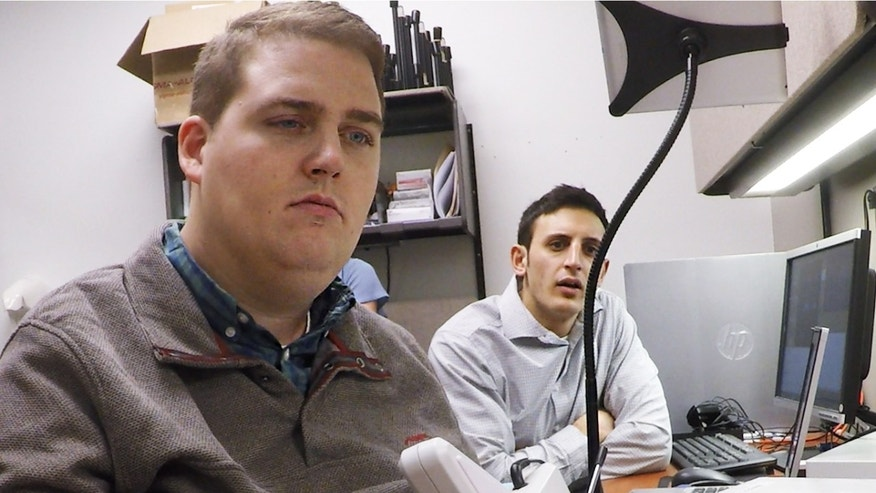 Nick Annetta, right, of Battelle, watches as Ian Burkhart, 24, plays a guitar video game using his paralyzed hand. A computer chip in Burkhart`s brain reads his thoughts, decodes them, then sends signals to a sleeve on his arm, that allows him to move his hand.