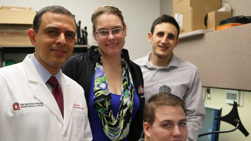 Patient Ian Burkhart, seated, poses with members of the research team (from left) Dr. Ali Rezai and Dr. Marcie Bockbrader of The Ohio State University Wexner Medical Center and Nick Annetta of Battelle during a neural bypass training session.