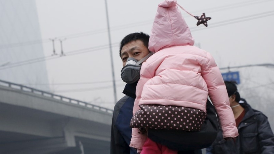 "A man wearing a mask carries his baby on his shoulder amid heavy smog after the city issued its first ever ""red alert"" for air pollution, in Beijing"