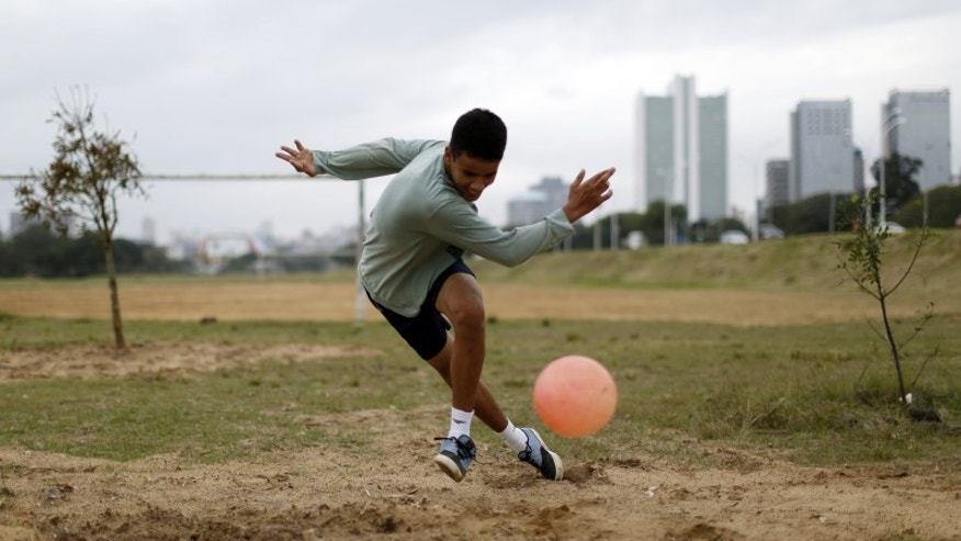 A boy plays soccer in a park in Porto Alegre