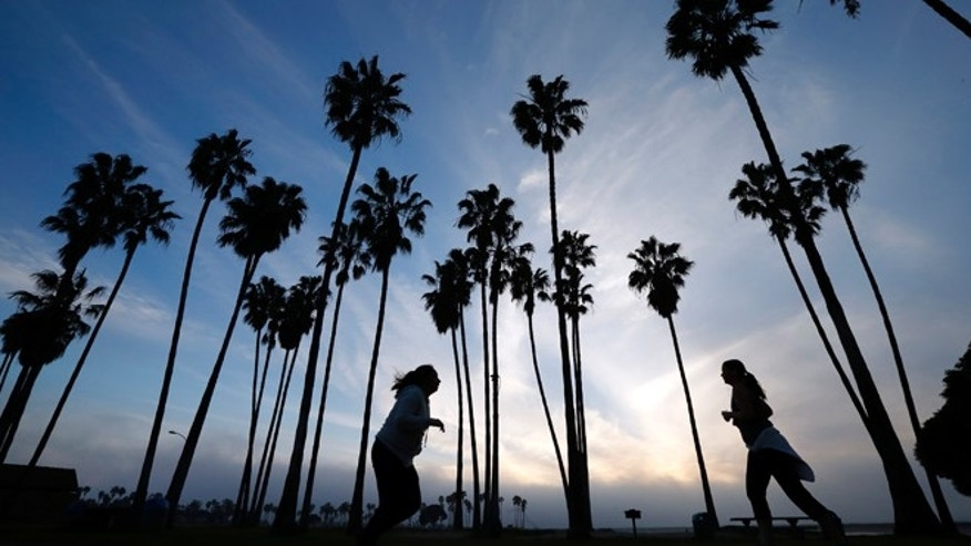 FILE - In this Feb. 23, 2016, file photo, women run as the sun sets in San Diego. Life expectancy for white women has fallen a little, according to a new government report.  The dip is small - white women lost about five weeks from their predicted lifespan in 2014, compared to 2013, the Centers for Disease Control and Prevention reported Wednesday, April 20, 2016. (AP Photo/Gregory Bull, File)