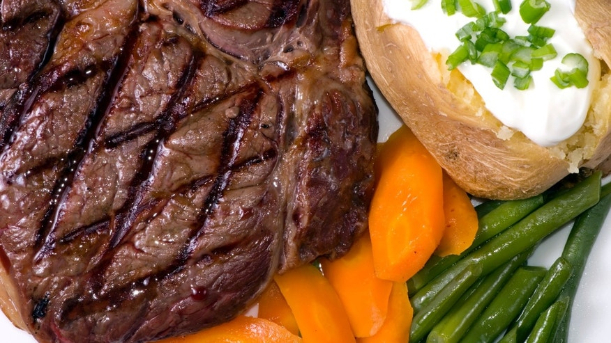 A grilled ribeye steak with a baked potato and vegetables