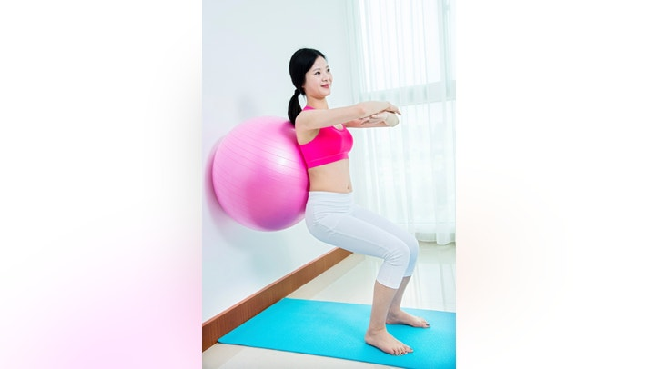 Young asian woman working out with fitness ball.