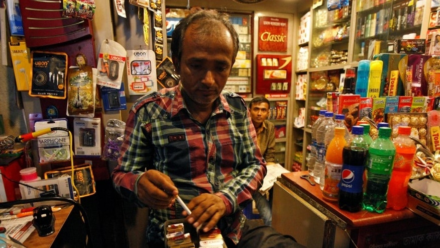 A shopkeeper takes out a cigarette from a box for a customer in Kolkata