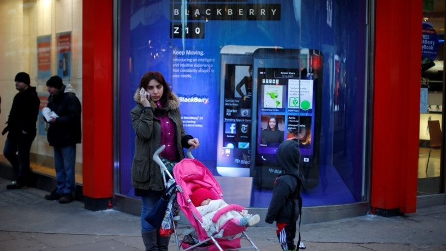 A woman uses her mobile phone outside a branch of UK retailer Phones 4U advertising the new Blackberry Z10 in central London