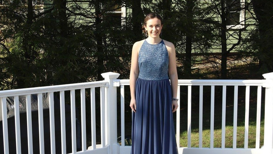 In this April 15, 2016 photo provided by Jennifer Goodwin, Jillian Dalton wears Catherine Malatesta's prom dress at her home in Arlington, Mass., before attending the Arlington High School prom. After Catherine died from a rare cancer on Aug. 2, 2015, her friends decided each of them would wear Catherine's gown to their own proms to honor her and remember the happiness she exuded on that special night. (Jennifer Goodwin via AP)