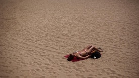 A woman sunbathes in a beach in Barcelona, Spain, Friday, May 15, 2015. The Iberian Peninsula has experienced record high temperatures for May as thermometers shot up to levels normally only seen in midsummer. (AP Photo/Emilio Morenatti)