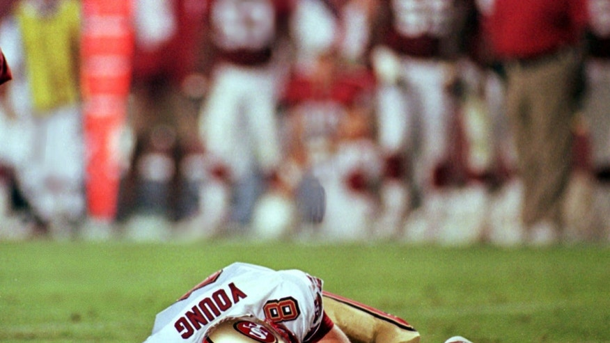 San Francisco 49ers' quarterback Steve Young lays motionless on field after suffering a concussion in the second quarter of the 49ers' game against the Arizona Cardinals Monday Sept. 27, 1999 in Tempe, Arizona.