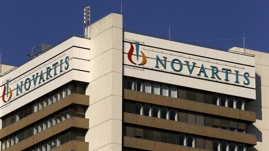 The logo of Swiss pharmaceutical company Novartis is seen on its headquarters building in Basel, Switzerland October 27, 2015. Novartis agreed in principle to pay $390 million to settle U.S. allegations that it used kickbacks to speciality pharmacies to push sales of some drugs, the Swiss company said on Tuesday, hitting third-quarter earnings. REUTERS/Arnd Wiegmann