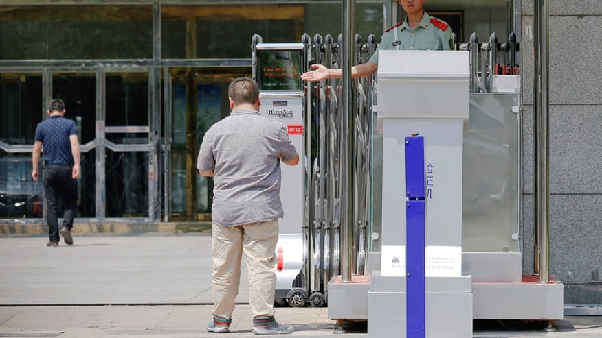 A security guard lets a man enter the building where the China's Food and Drug Administration main office is located in Beijing