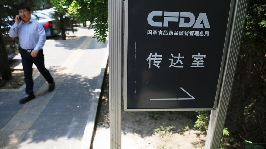 A man talks on the phone near a sign for the reception office of China's Food and Drug Administration in Beijing