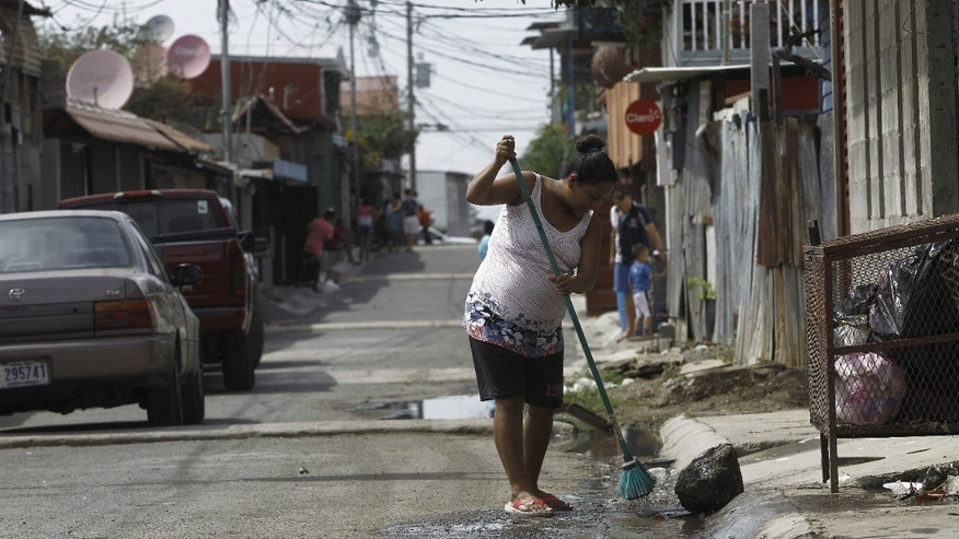 A pregnant woman cleans a street wet with water flowing from houses as health workers fumigate to help control the spread of the mosquito-borne Zika virus, in a slum of San Jose, Costa Rica February 3, 2016. REUTERS/Juan Carlos Ulate - RTX25CBN