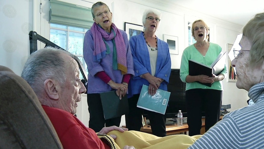 May 2, 2016: In this still image from video, members of JourneySongs choir sing for Norman Doelling, left, and his wife Jean at their home in Newton, Mass.