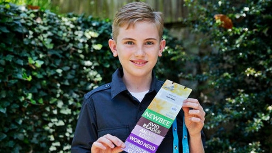 Neil Maes, 11, of Belton, S.C., holds up his National Spelling Bee badge at The Alexander Graham Bell Association for the Deaf and Hard of Hearing (AG Bell) in Washington, Tuesday, May 24, 2016.