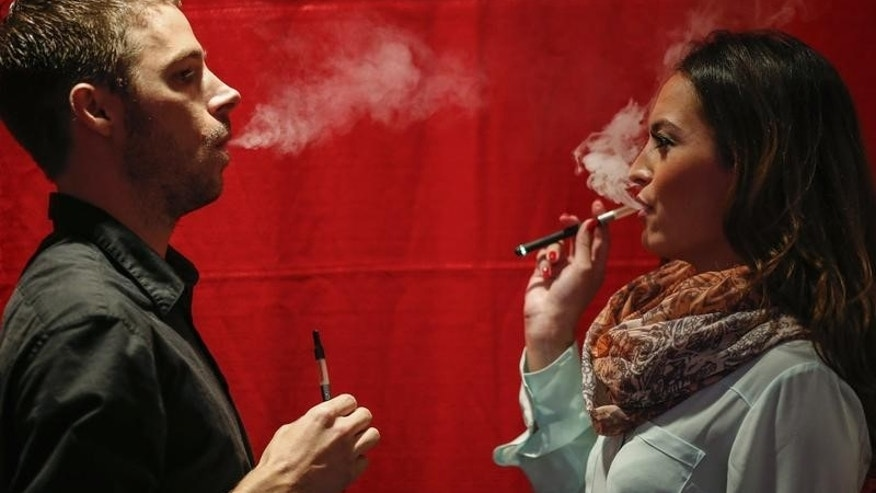 People use electronic vaporizers with cannabidiol (CBD)-rich hemp oil while attending the International Cannabis Association Convention in New York