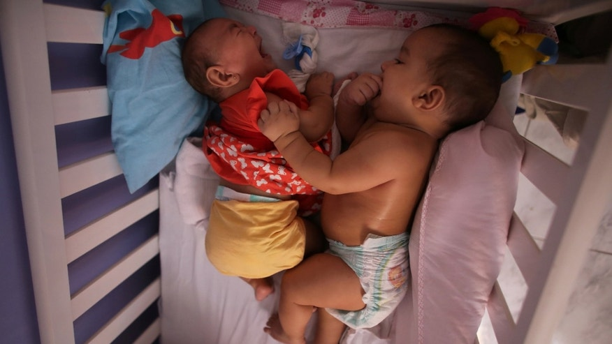 Five-month-old twins, Laura (L) and Lucas lie in their bed at their house in Santos, Sao Paulo state, Brazil.