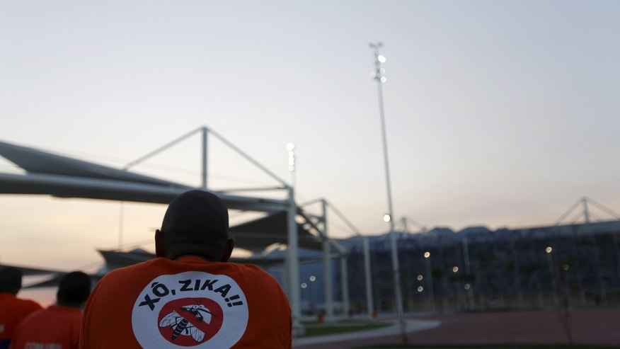 """April 11, 2016: A worker from a public cleaning company wears a T-shirt that reads """"Out Zika"""" is pictured before the inauguration ceremony of the common areas at the Live Site at the 2016 Rio Olympics park in Rio de Janeiro, Brazil."""