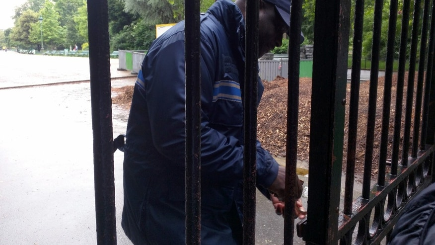 A city of Paris locks the gate to the Park Monceau, following a lightning strike, in Paris, Saturday, May 28, 2016. A Paris fire service spokesman says 11 people including eight children have been hit by lightning in a Paris park after a sudden spring storm overtook a child's birthday party. The victims had sought shelter Saturday under a tree at Park Monceau, a popular weekend hangout for well-to-do families in Paris. (AP Photo/Raphael Satter)