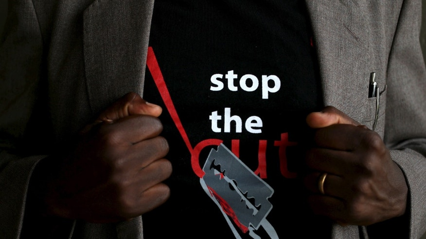 "A man shows the logo of a T-shirt that reads ""Stop the Cut"" referring to Female Genital Mutilation (FGM) during a social event advocating against harmful practices such as FGM at the Imbirikani Girls High School in Imbirikani, Kenya, April 21, 2016. REUTERS/Siegfried Modola - RTX2B0S7"