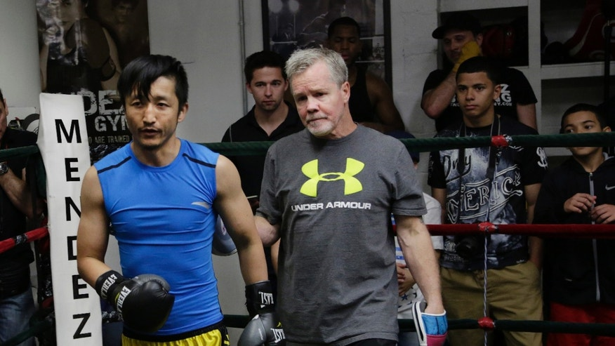 Zou Shiming, left, a two-time Olympic gold medalist and three-time World Amateur Champion from China, exits the ring with trainer Freddie Roach after a workout, Wednesday, June 8, 2016, at Mendez Gym in New York. Zou will be defending his WBO International flyweight title and No. 2 world rating in a 10-round bout against Jozsef Ajtai of Hungary,Saturday, June 11 at Madison Square Garden. (AP Photo/Mark Lennihan)