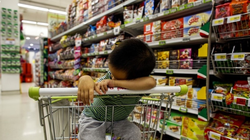 A boy sleeps in a shopping cart at a department store in Bangkok