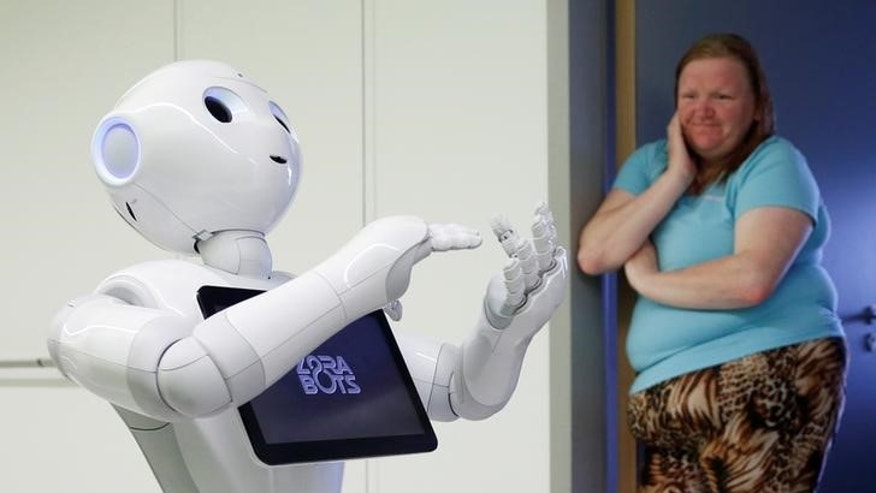 "A visitor watches new recruit ""Pepper"" the robot at AZ Damiaan hospital in Ostend"