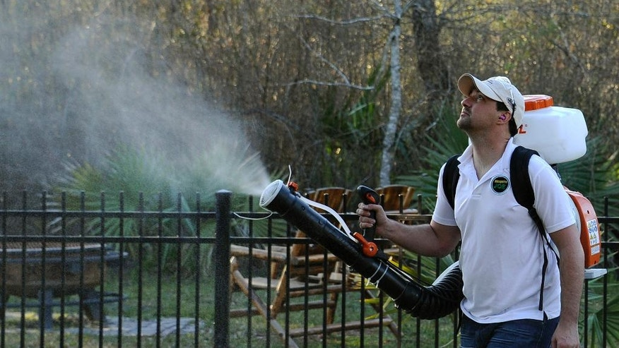 In this Wednesday, Feb. 10, 2016 file photo, Darryl Nevins, owner of a Mosquito Joe franchise, sprays a backyard to control mosquitoes in Houston. Zika has been sweeping through Latin America and the Caribbean in recent months, and the fear is that it will get worse there and arrive in the U.S. with the onset of mosquito season this summer. (AP Photo/Pat Sullivan)