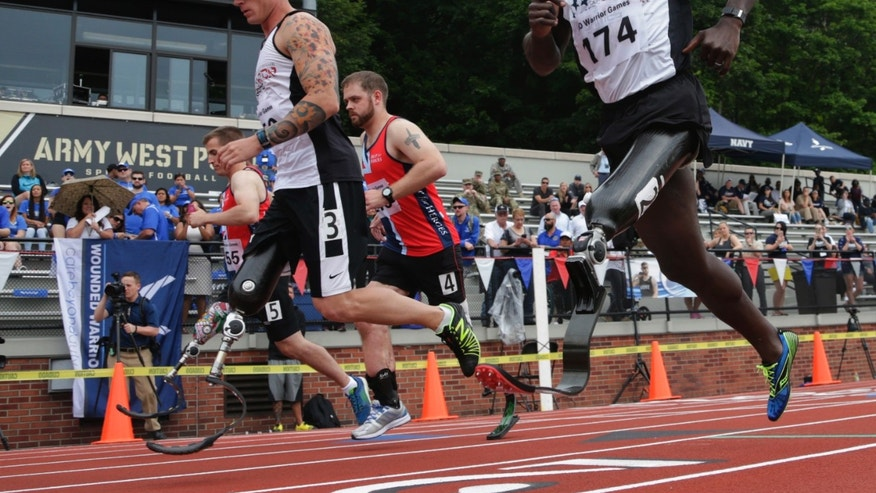 In this Thursday, June 16, 2016 photo, William Reynolds, right, a 2002 graduate of the U.S. Military Academy, competes in the 800-meter race at the Warrior Games in West Point, N.Y. Reynolds said his training and discipline are the same as when he was a competitive gymnast as a West Point cadet. The big adjustment was learning to run when he didn't have the sensation of his left foot hitting the ground anymore. (AP Photo/Mike Groll)