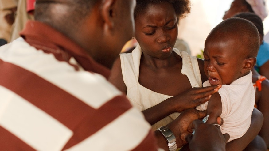 FILE- In this Saturday, Jan. 22, 2011 file photo, a health worker injects a young boy with yellow fever vaccine in Seguela in northern Ivory Coast. On Thursday, May 19, 2016 the UN health agency convened an expert committee to consider whether the epidemic of yellow fever, an acute viral hemorrhagic fever, qualifies as an international public health emergency. (AP Photo/Olivier Asselin, File)