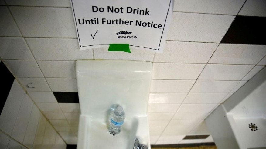 A sign is seen next to a water dispenser at North Western High School in Flint, a city struggling with the effects of lead-poisoned drinking water in Michigan