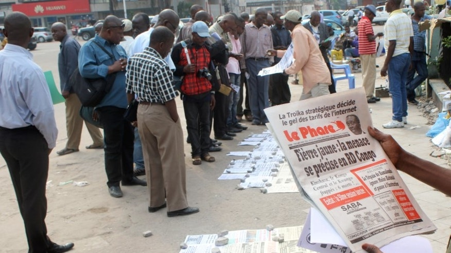 Residents read newspapers with reports of Yellow Fever, in Kinshasa