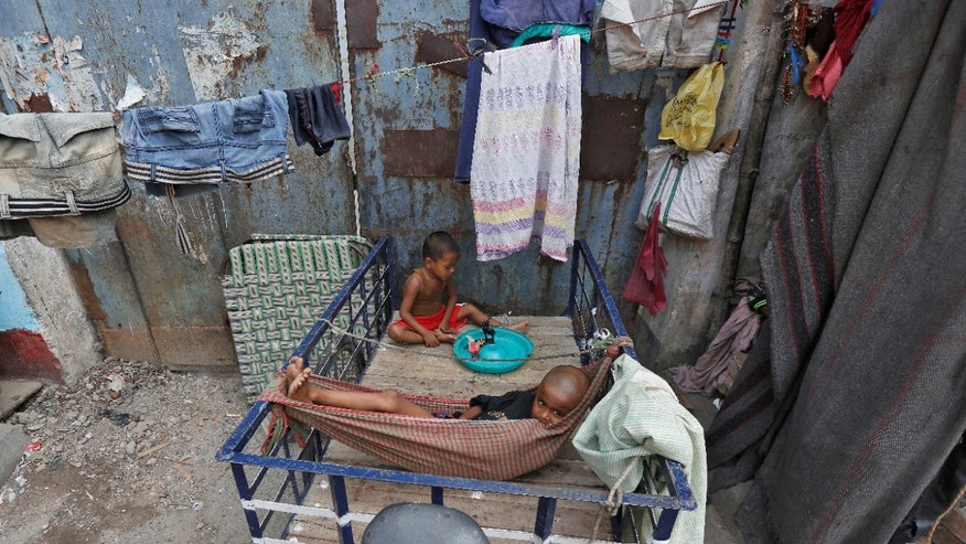 Homeless children play on their father's rickshaw at a roadside in Kolkata, India May 18, 2016. REUTERS/Rupak De Chowdhuri - RTSESGM