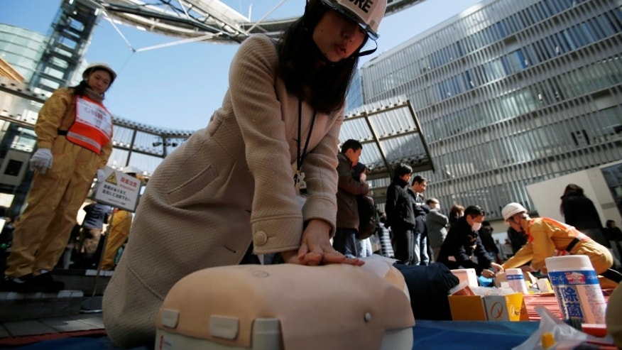 Participants practice cardiopulmonary resuscitation (CPR) during a disaster drill at the Roppongi Hills complex in Tokyo