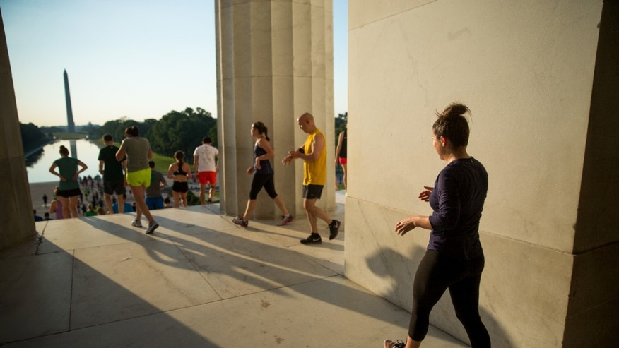 "In this May 25, 2016 photo, members of the running group ""November Project"" run up and down the stairs of the Lincoln Memorial, in Washington. Fitness buffs around the country are bringing the 'take the stairs' advice to a whole new level as noteworthy landmarks have become unlikely, yet popular new workout sites."