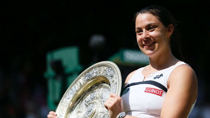 Marion Bartoli of France holds her winners trophy, the Venus Rosewater Dish, after defeating Sabine Lisicki of Germany in their women's singles final tennis match at the Wimbledon Tennis Championships, in London July 6, 2013.          REUTERS/Stefan Wermuth (BRITAIN  - Tags: SPORT TENNIS)   - RTX11EQZ
