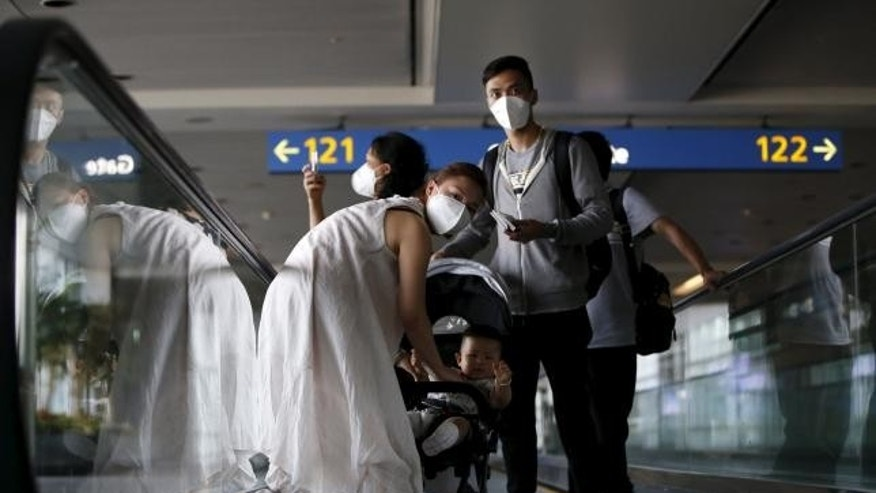 June 2, 2015: Passengers wearing masks to prevent contracting Middle East Respiratory Syndrome (MERS) ride on a travelator upon arrival at Incheon International Airport in Incheon, South Korea.