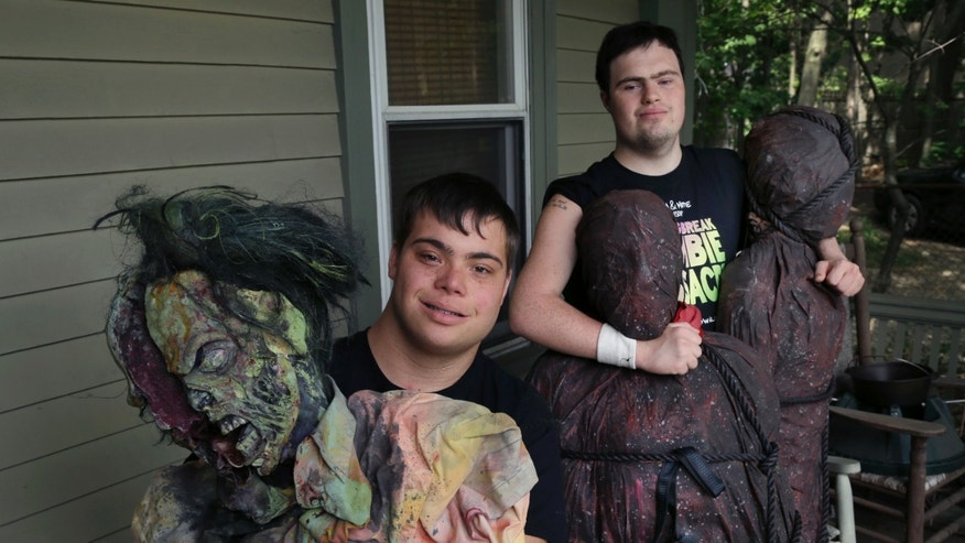In this July 12, 2016 photo, Mattie Zufelt, left, and Sam Suchmann pose with ghoulish figures at Sam's home in Providence, R.I. Suchmann and Zufelt, best friends with Down syndrome, are living their dreams of making a full-length, epic zombie movie and becoming celebrities.