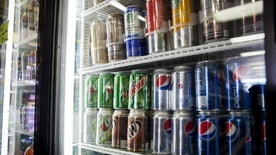 Cans of soda are displayed in a case at Kwik Stops Liquor in San Diego, California February 13, 2014. REUTERS/Sam Hodgson/Files