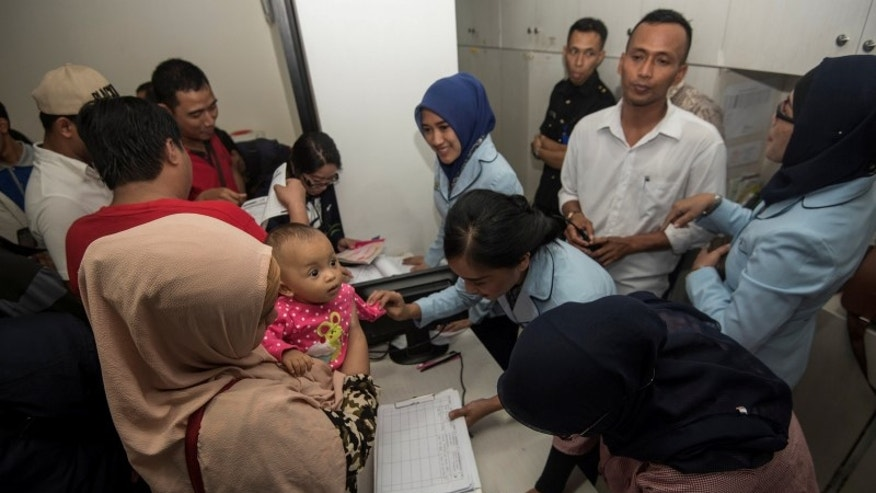 Hospital workers collect information from parents who believe their children may have received fake vaccines at a hospital in East Jakarta, Indonesia
