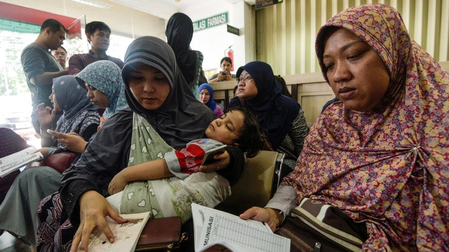 Women wait for information about the alleged use of fake vaccines on their children at a hospital in East Jakarta, Indonesia