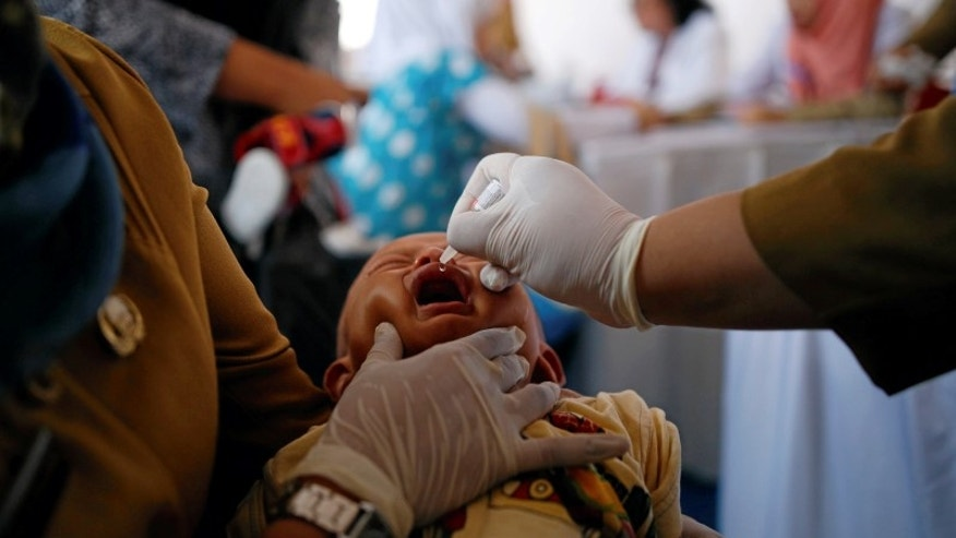 A child is revaccinated by government healthcare workers at a clinic in East Jakarta
