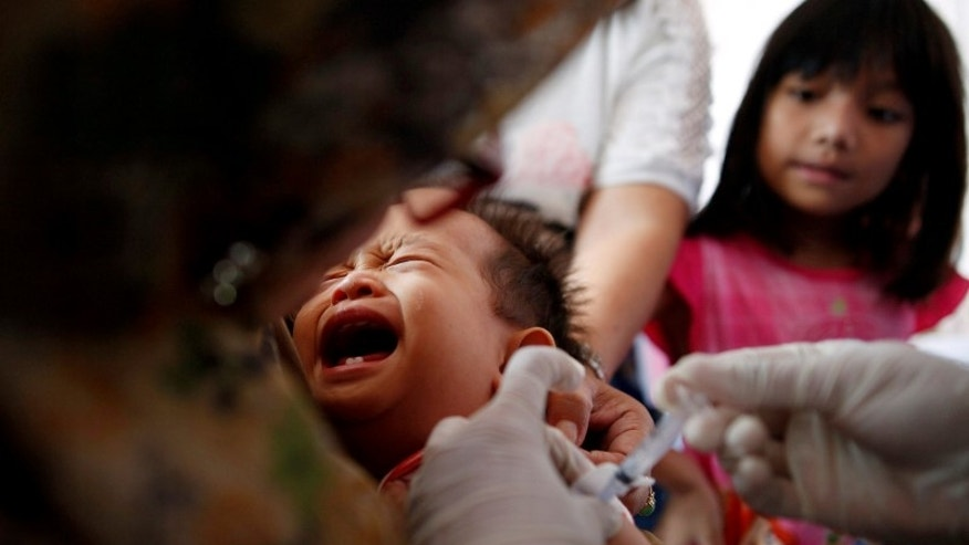 A child is revaccinated by healthcare workers at a clinic in East Jakarta
