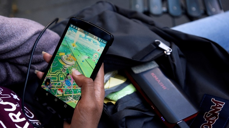 A woman uses a portable battery pack to charge her phone while playing the augmented reality mobile game Pokemon GO by Nintendo in New York City, U.S. July 11, 2016.