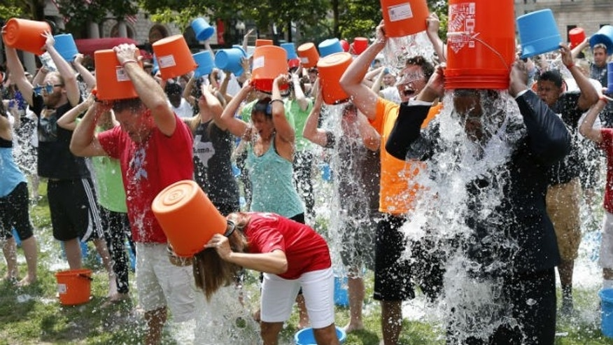 Boston City Councillor Tito Jackson, right, leads some 200 people in the ice bucket challenge at Boston's Copley Square, Thursday, Aug. 7, 2014 to raise funds and awareness for ALS. (AP Photo/Elise Amendola)