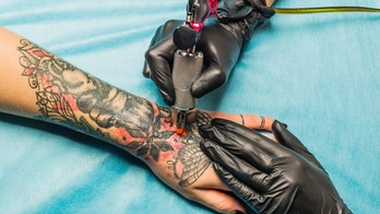 Close up tattoo artist demonstrates the process of getting black and red tattoo with orange paint. Master works on the professional blue mat in black sterile gloves.