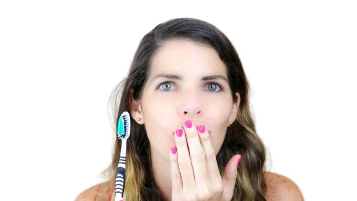 Closeup of an attractive young woman with a toothbrush