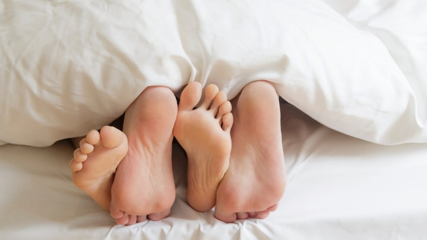 couple feet in bed sex istock